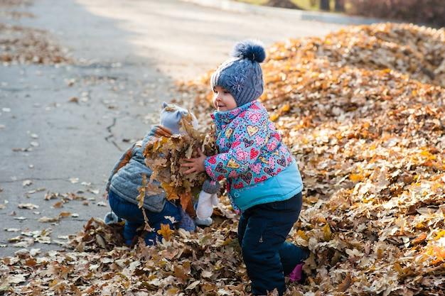 Девушка играет с листьями в парке