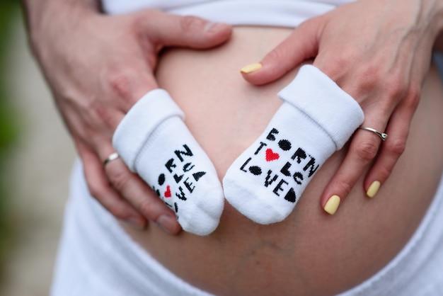 健康的な妊娠の概念。妊娠中の女性は彼女の赤ちゃんのバンプにハートの形で彼女の手を繋いでいます。