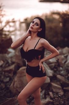 黒い砂のビーチで休んで黒い水着の若いセクシーなスポーティな女の子。オーシャンショアで美しい女性