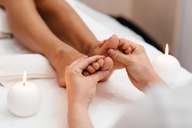 Массажист делает массаж ног в спа салоне.