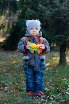 Ребенок с игрушкой в руках гуляет по парку