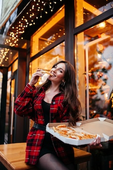 焼きたてのピザを楽しんでいるテーブルに座っている若い幸せな白人カップル私