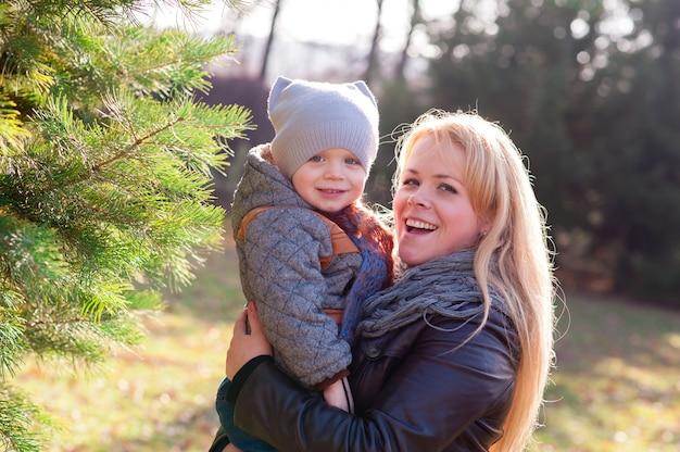 母と息子の秋の公園で遊ぶ