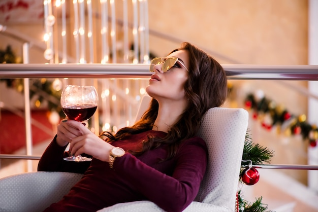 夜の光と雪の背景の上にスパークリングワインのグラスとイブニングドレスの笑顔の女性