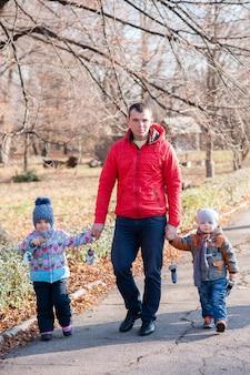 公園を歩く子供たちとの父