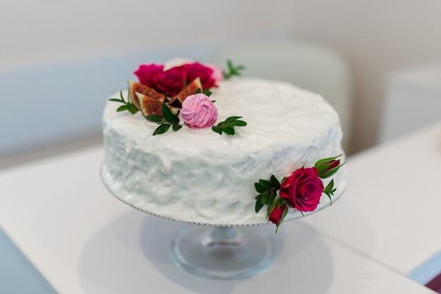 赤い花を持つ白いケーキ。白色の背景