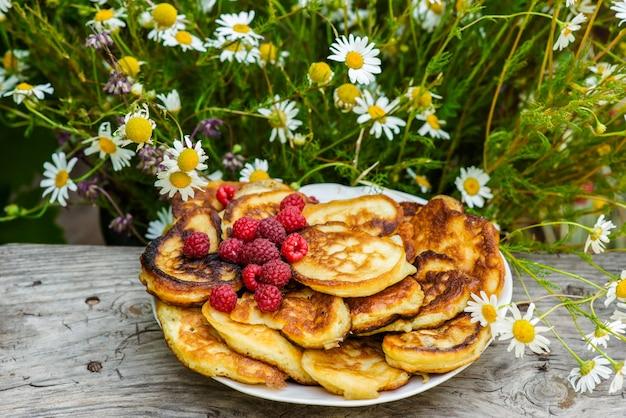 花と木のテーブルに果実を焼くの静物画。