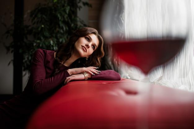 レストランで赤ワインのグラスを持つエレガントなブルネットの女性。