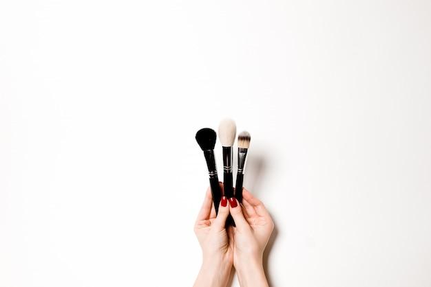 白い背景で隔離された女性の手の美容師のプロのメイクアップブラシ化粧品