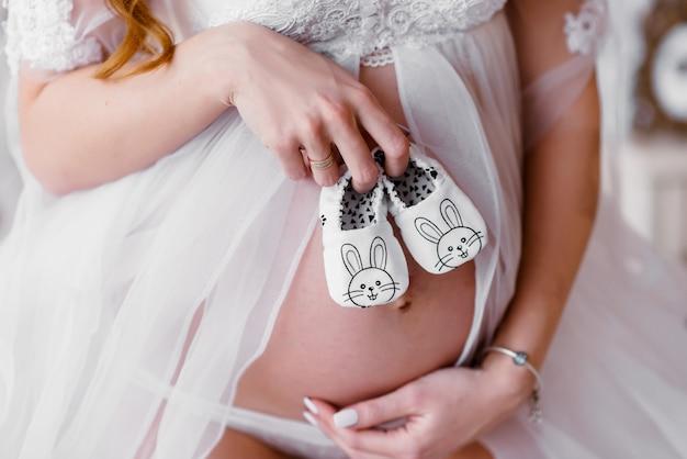 赤ちゃんの靴下、生まれたばかりの赤ちゃんの靴下、生まれたばかりの赤ちゃんを持つ母親の手で妊娠中の女性の腹