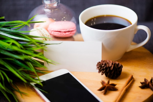 スマートフォン、ノートブックの上にペン、名刺、一杯のコーヒーと花のオフィスデスクテーブル。