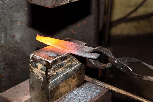 金属製品をハンマーで鍛造する。
