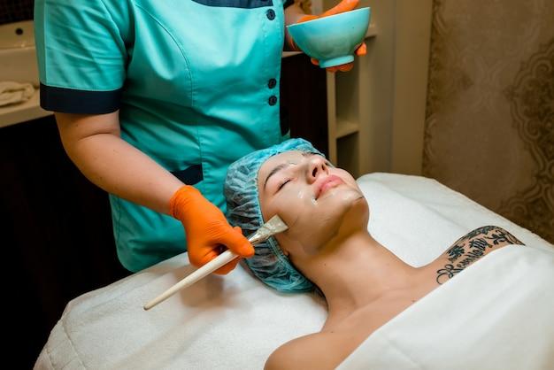 美しい顔の肌のためのゴールドマスクを剥離します。患者のための美容処置をしている美容師。