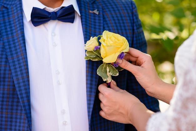 花嫁はブートニアの新郎を着ています。