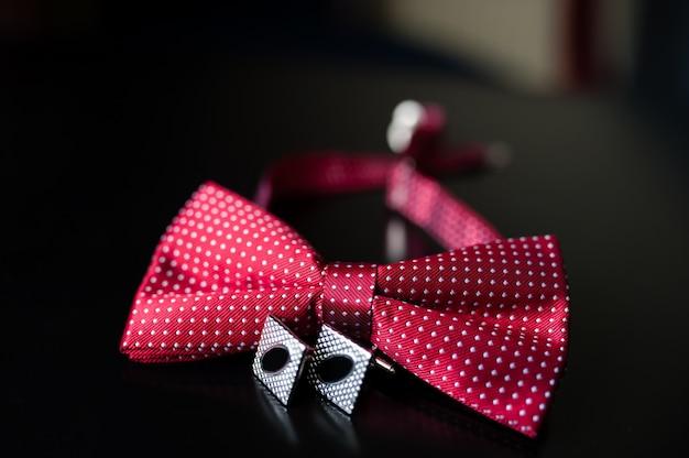 Красивый красный галстук-бабочка и запонки.