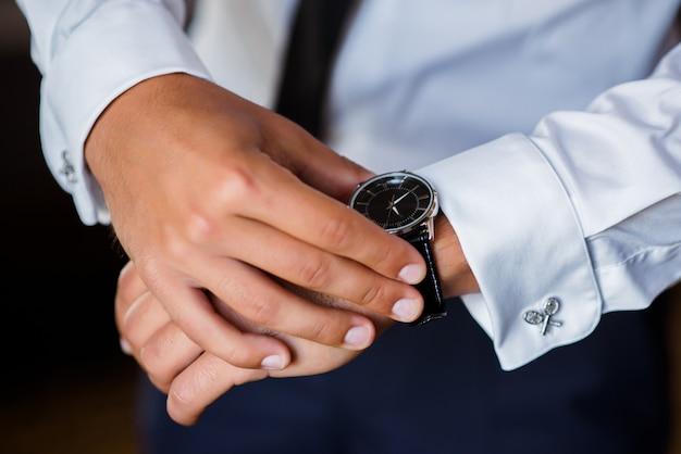 青いスーツを着た男は時計の時間を見ています。