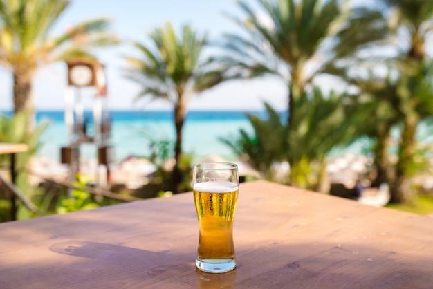 海に対して木製のテーブルの上のビールのグラス。