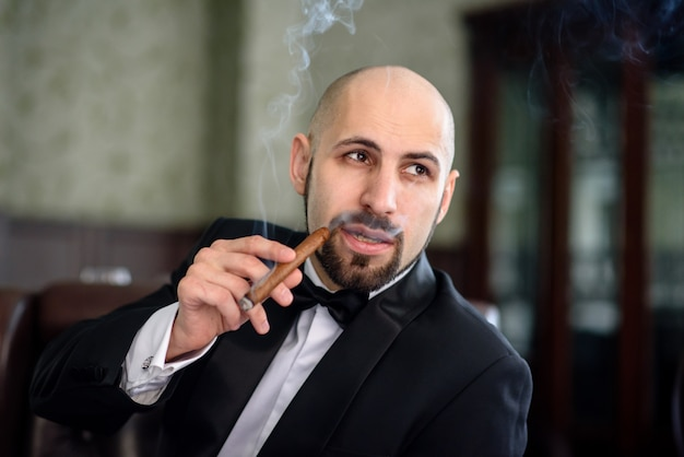 ドレスコートを着た残忍な男が葉巻を吸います。