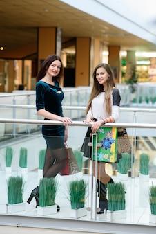 Счастливые девушки делают покупки в торговом центре.