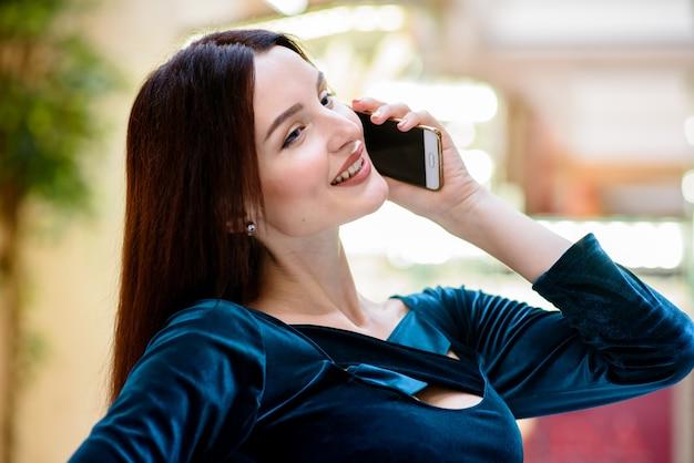 少女はモールで電話で話しています。
