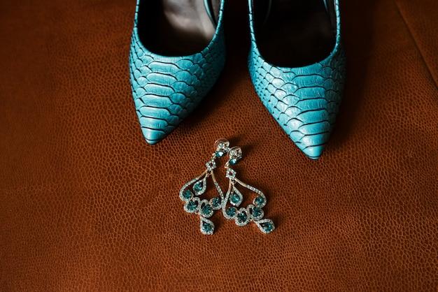 Синие женские туфли и серьги.