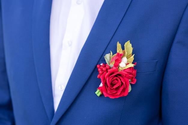 青いジャケットの赤いブートニア。
