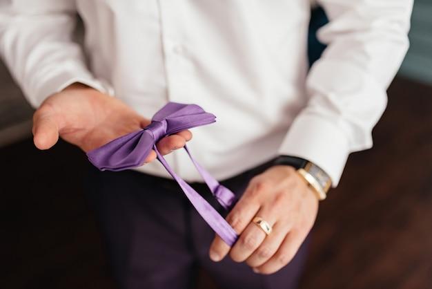 男が手に蝶ネクタイを抱いています。