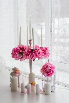キャンドルと花の美しい装飾。ホワイトピンクの色合い。