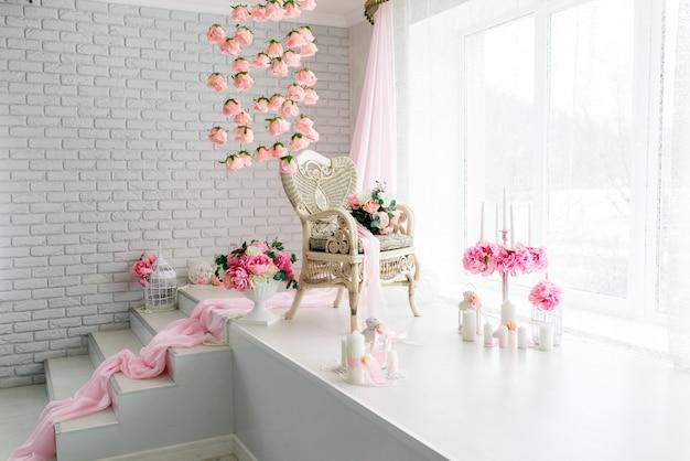 花で飾られたレトロなテーブルと椅子のある白い部屋。