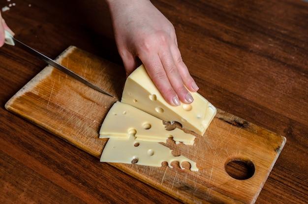 木の板にチーズをスライスします。