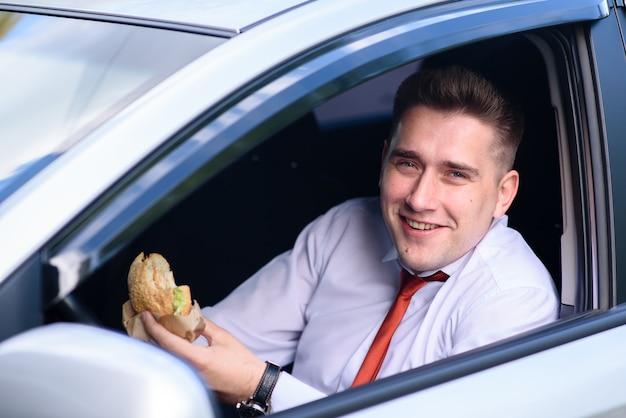 Бизнесмен обедает и пьет кофе в машине.