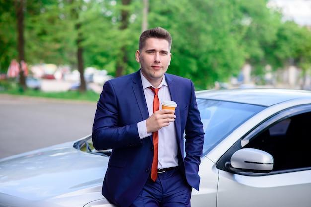 ビジネスマンが車の中でコーヒーを飲みます。