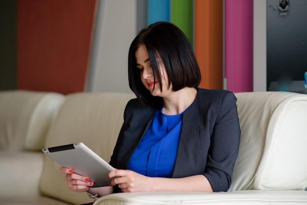 美しいビジネス女性のラップトップおよびタブレットでの作業。