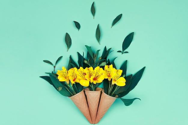 緑の黄色の花の花束は、デザインの青い背景にワッフルコーンに葉します。