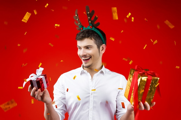 Новый год вечеринка концепция счастливое веселье улыбающийся очаровательный красивый хипстер мужчина парень мужчина празднует зимние рождественские праздники носить олень рог шляпу держит подарки коробка подарка золотой конфетти