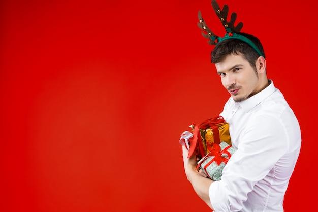 新年パーティーコンセプト幸せな笑みを浮かべて魅力的なハンサムな流行に敏感な男男冬の祝日を祝う白いシャツを着て鹿ホーン帽子を保持貪欲なプレゼントボックスギフト赤背景