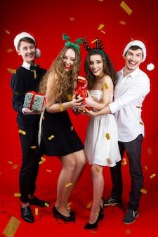 おとぎ話のカーニバルの衣装を着て新年パーティーコンセプト幸せな笑顔の友人ヒップスター会社サンタ鹿クリスマスツリー帽子楽しい戦いプレゼント冬の祝日を祝う紙吹雪