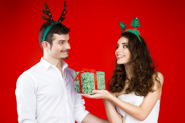 おとぎ話のカーニバルの衣装鹿クリスマスツリーの帽子を身に着けている流行に敏感なカップルの友人を笑顔新年パーティーコンセプト幸せ楽しい冬の休日を祝うプレゼント驚きを与える