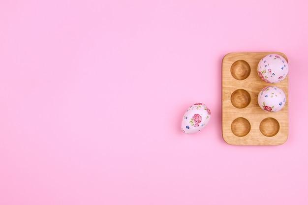 Счастливой пасхи. традиция пасхальные большие и маленькие яйца с рисунком весеннего цветка в деревянной подставке на розовом фоне