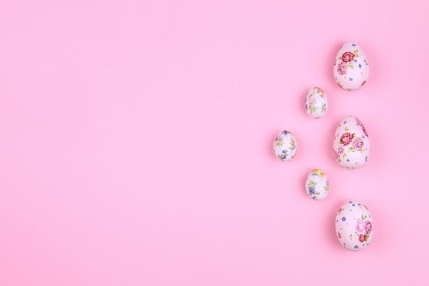Счастливой пасхи. традиция пасхальные большие и маленькие яйца с рисунком весеннего цветка на розовом фоне