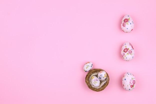 Счастливой пасхи. традиция пасхальные большие и маленькие яйца с рисунком весеннего цветка в деревянном гнезде на розовом фоне