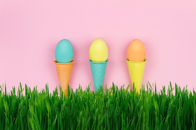 Счастливой пасхи концепция. желтые синие оранжевые яйца на зеленой траве