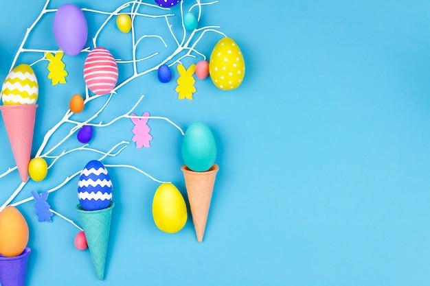 ハッピーイースターのコンセプト。カラフルなイースターエッグ、ワッフルコーン、青の背景にウサギのシルエットと春の木の枝