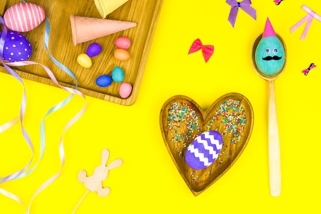 Счастливой пасхи концепция. деревянные тарелки в форме сердца, квадрат с разноцветными пасхальными яйцами с комичным лицом