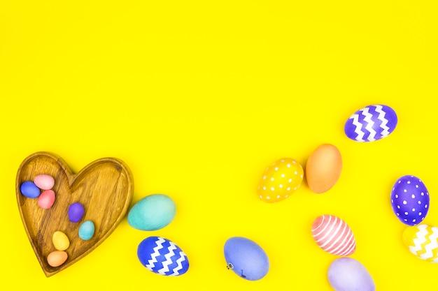 Счастливой пасхи концепция. деревянные тарелки в форме сердца, квадрат с красочными пасхальными яйцами с комическим лицом на желтом фоне