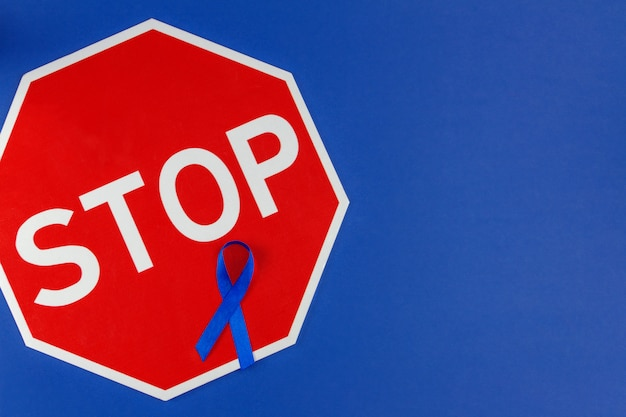 世界がんの日の概念。腸癌と記号のシンボルとして青いリボンは、暗い青色の背景に分離を停止します。