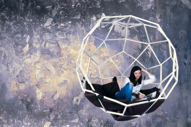 ファッションデザイナーの女性の図面を持つ女性の女の子は、枕と未来的な構造スイング球体のデザインスタジオで働くスケッチをドラフトします。