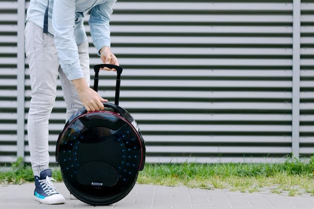 生態学的な電気輸送未来的なエコ電気一輪車スクーター、電動ホイールのバランスをとる現代の若い成人男性ビジネスマン学生フリーランサー。エコプラネット、未来は今のコンセプトです。