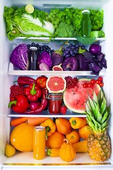 Свежая органическая здоровая сырая антиоксидантная фиолетовая, красная, зеленая, оранжевая и желтая пища, овощи, фрукты и соки у вегетарианца вегетарианца открыли полный холодильник витаминов. здоровое питание, диета и образ жизни.