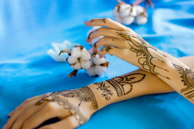 伝統的なインドの東洋の一時的な刺青の飾りで描かれたクローズアップのほっそりした女性の手首。ヘナのタトゥーで飾られた女性の手。ひだ、背景に綿の花とスカイブルーの生地。